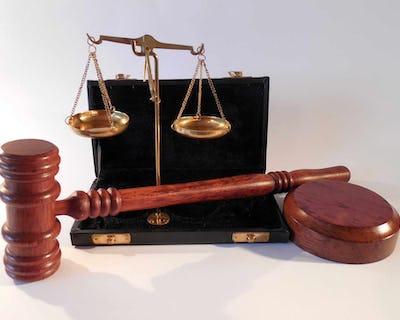 En ordförandeklubba tillsammans med en våg som symboliserar rättvisa.