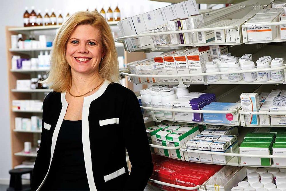 Annika Svedberg står framför en hylla med apoteksprodukter.