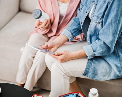 Två personer sitter i en soffa, den ena med en medicinburk i handen.