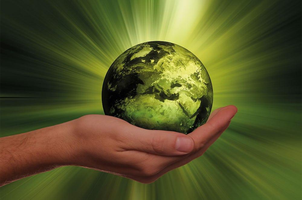 En hand håller i en grön planeten Jorden.